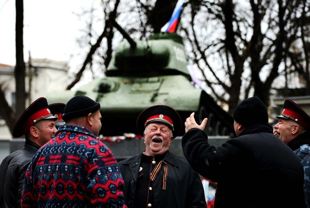 Cossacks share a laugh next to a war monument at a gathering of pro-Russian supporters outside the Crimean parliament building in Simferopol, Ukraine, on February 28, 2014. According to media reports Russian soldiers have occupied the airport at nearby Sevastapol while soldiers whose identity could not be confirmed have stationed themselves at Simferopol International Airport in moves that are raising tensions between Russia and the new Kiev government. (Photo by Sean Gallup/Getty Images)