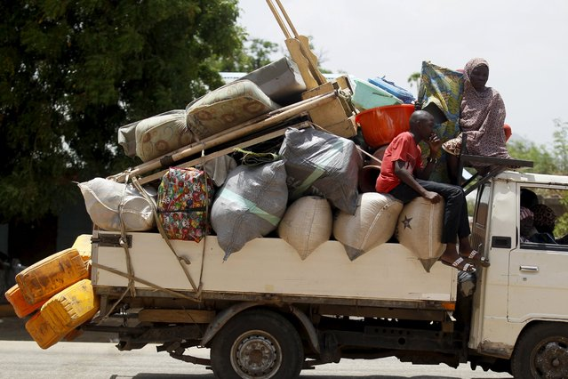 People travel in a truck with their belongings as they return after the Nigerian military recaptures the town of Michika from Boko Haram, Adamawa state May 10, 2015. (Photo by Akintunde Akinleye/Reuters)