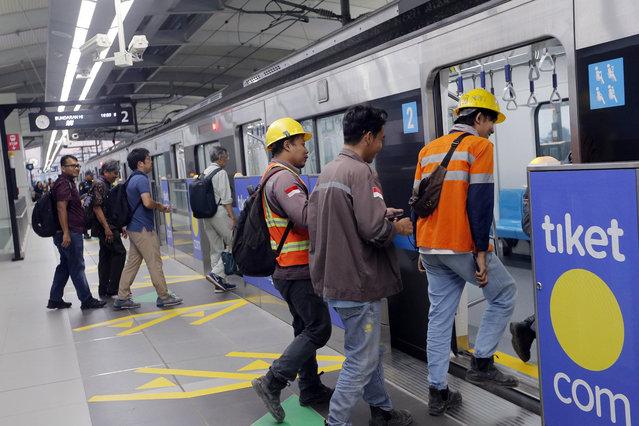 In this March 15, 2019, photo, passengers get on a Mass Rapid Transit (MRT) during a trial run in Jakarta, Indonesia. Commuting in the gridlocked Indonesian capital will for some involve less frustration, sweat and fumes when its first subway line opens later this month. The 10-mile system running south from Jakarta's downtown is the first phase of a development that if fully realized will plant a cross-shaped network of stations in the teeming city of 30 million people. (Photo by Tatan Syuflana/AP Photo)