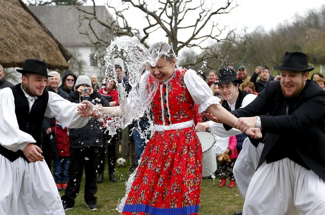 Men throw water on a woman as part of traditional Easter celebrations in Szenna, Hungary, March 28, 2016. (Photo by Laszlo Balogh/Reuters)