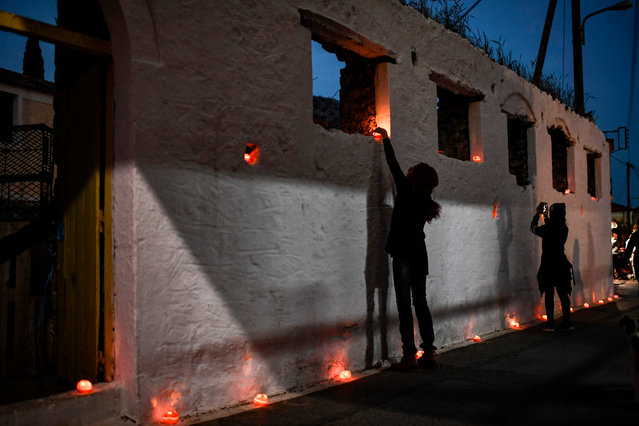 "People decorate a street with candles inside oranges during the Epitaph ceremony during Good Friday's ""Apokathelosis"", the Descent of Christ's dead body from the Cross, which forms a key part of Orthodox Easter, in the southern city of Leonidio, at the Peloponnese peninsula on April 26, 2019. Millions of Greeks flock to churches around the country this week to celebrate Easter, the country's foremost religious celebration. (Photo by Aris Messinis/AFP Photo)"