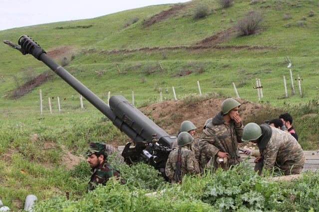 Karabakh Armenian soldiers stand near a howitzer in Hadrut province in Nagorno-Karabakh, Azerbaijan, Tuesday, April 5, 2016. Azerbaijan forces and separatist forces in Nagorno-Karabakh agreed on a cease-fire Tuesday following three days of the heaviest fighting in the region since 1994, the Azeri defense ministry announced. (Photo by Albert Khachatryan/Photolure via AP Photo)