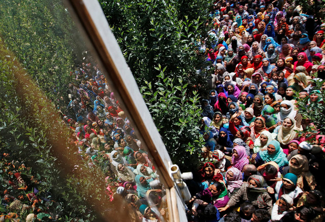 People watch the body of Imran Ahmad Bhat, a suspected militant, who was killed during a gun battle with Indian security forces today, during his funeral procession in Arihal village in South Kashmir's Pulwama district on June 7, 2019. (Photo by Danish Ismail/Reuters)
