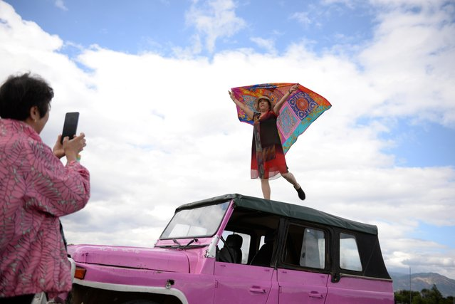 A woman poses with a scarf on the top of a car which serves as a prop near Erhai Lake in Dali Bai Autonomous Prefecture, Yunnan province, China on June 15, 2019. (Photo by Tingshu Wang/Reuters)