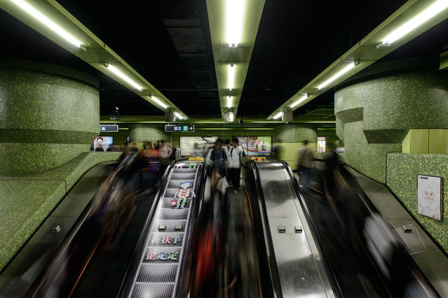 Commuters use escalators leading to a platform in a subway station in Hong Kong on February 26, 2014.  Hong Kong is pondering whether to rip out some seats from overcrowded metro trains to give the city's smartphone-addicted population more room to interact with their devices. (Photo by Philippe Lopez/AFP Photo)