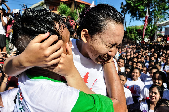 """A young Balinese man tries to kiss a woman during the Kissing Festival known as """"Omed-Omedan"""" at Sesetan village on April 1, 2014 in Denpasar, Bali, Indonesia. The kissing festival is held annually, one day after Balinese Hindus celebrate the Nyepi Day of Silence. During the festival, Balinese youths gather first to pray, then to kiss and dance as spectators douse the teenagers with water. The festival is intended to fend off bad luck in the year ahead. (Photo by Agung Parameswara/Getty Images)"""