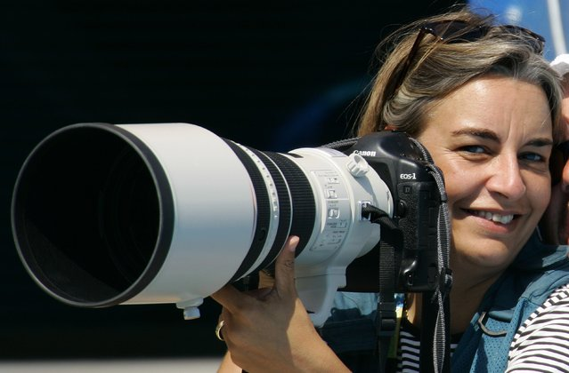 AP photographer Anja Niedringhaus laughs as she attends a swimming event at the 2004 Olympic Games in Athens, August 21, 2004. Niedringhaus, a veteran Associated Press photographer who had covered wars around the world was shot dead and another reporter was wounded on April 4, 2014 when an Afghan policeman opened fire on them in eastern Afghanistan, the news agency said. Picture taken August 21, 2004. (Photo by Reuters/Staff)