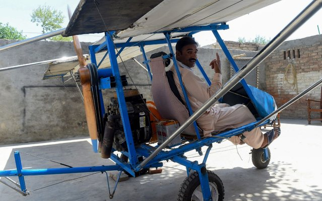 In this picture taken on April 8, 2019, Pakistani villager Muhammad Fayyaz poses for photographs as he sits in his small plane at his residence in Tabur village in central Punjab province. The engine is from a roadcutter, the wings are burlap, the wheels are borrowed from a rickshaw: a Pakistani popcorn seller has caught the attention of the Air Force by building his own plane. (Photo by Arif Ali/AFP Photo)