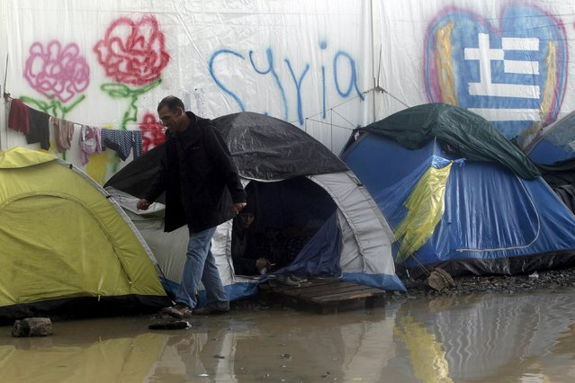 A refugee walks next to tents following heavy rainfall at a makeshift camp for migrants and refugees at the Greek-Macedonian border near the village of Idomeni, Greece, April 24, 2016. (Photo by Alexandros Avramidis/Reuters)