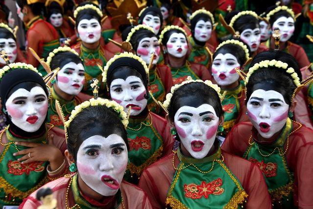 Dancers reacts to camera before they perform a Thengul dance during a festival in Bojonegoro, East Java province, Indonesia, July 14, 2019. (Photo by Zabur Karuru/Antara Foto via Reuters)