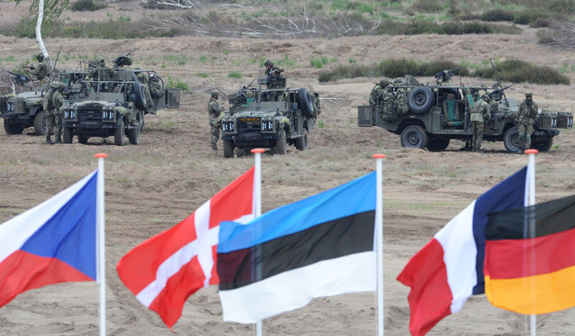Flags wave in front of soldiers who take positions with their army vehicles during the NATO Noble Jump exercise on a training range near Swietoszow Zagan, Poland, Thursday, June 18, 2015. (AP Photo/Alik Keplicz)