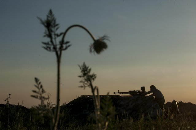 In this photo taken Monday, June 22, 2015, a Ukrainian serviceman from the Kiev-2 volunteer battalion fires a machine gun at the frontline in the village of Krymske, east Ukraine. (Photo by Evgeniy Maloletka/AP Photo)