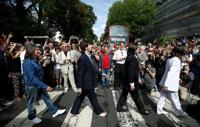 People take pictures as the Beatles cover band members walk on the zebra crossing on Abbey Road in London, Britain on August 8, 2019. Hundreds of people gathered at the world's most famous zebra crossing on Thursday to mark the 50th anniversary of the day the Beatles were photographed on it, creating one of the best-known album covers in music history and an image imitated by countless fans ever since. (Photo by Henry Nicholls/Reuters)