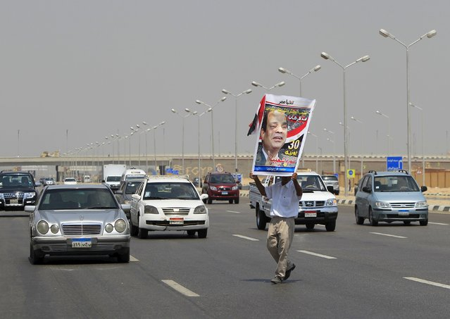 A man carries a portrait of Egyptian President Abdel Fattah al-Sisi as he crosses a street to the funeral of Egyptian public prosecutor Hisham Barakat, on the second anniversary of the June 30 protests, in Cairo, Egypt, June 30, 2015. (Photo by Mohamed Abd El Ghany/Reuters)