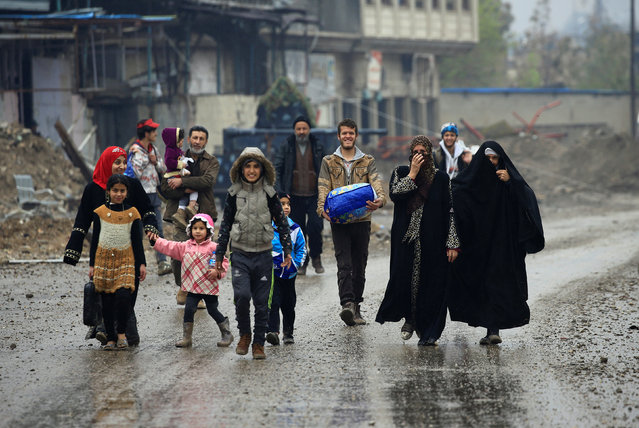 Displaced Iraqi people from Laagada district of Mosul react after they reach safe areas, as Iraqi forces battle with Islamic State militants in the city of Mosul, Iraq, March 23, 2017. (Photo by Youssef Boudlal/Reuters)
