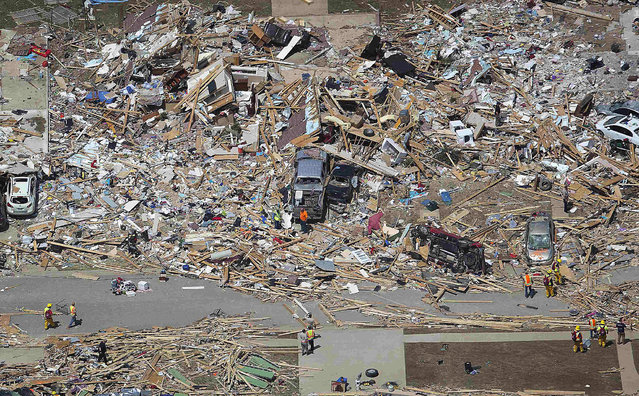 People sift through the rubble of what is left of homes after a tornado hit the town of Vilonia, Arkansas April 28, 2014. Workers searched for survivors on Monday in the rubble left by a wave of tornadoes that ripped through the south-central United States a day earlier, killing at least 18 people in Arkansas, Oklahoma and Iowa. (Photo by Carlo Allegri/Reuters)
