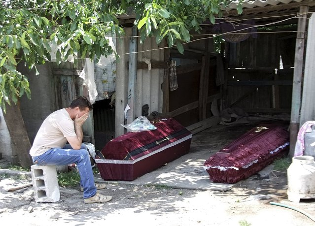 A man, whose mother according to locals was killed by an early morning shelling, reacts while sitting near her coffin, outside the damaged house before her funeral in Donetsk, Ukraine, July 7, 2015. Two residents, including the man's mother, were killed by shelling and buried later on Tuesday, according to local journalists. (Photo by Igor Tkachenko/Reuters)