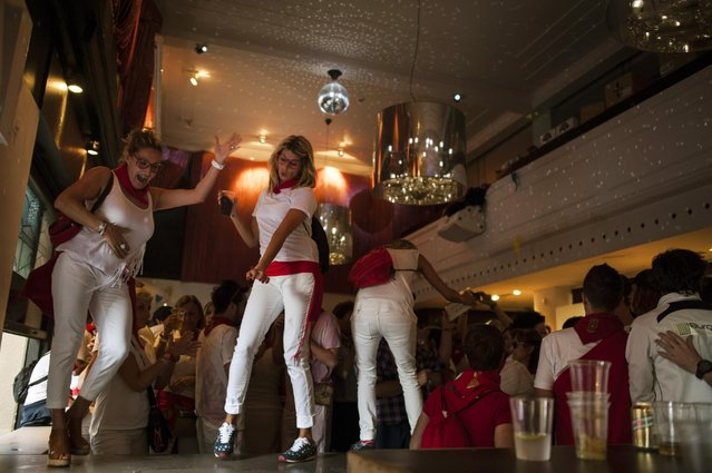 In this photo taken Wednesday, July 8, 2015, people enjoy the evening dancing inside a bar, at the San Fermin Festival, in Pamplona, Spain. Revelers from around the world arrive to Pamplona every year to take part in some of the eight days of the running of the bulls. (Photo by Alvaro Barrientos/AP Photo)