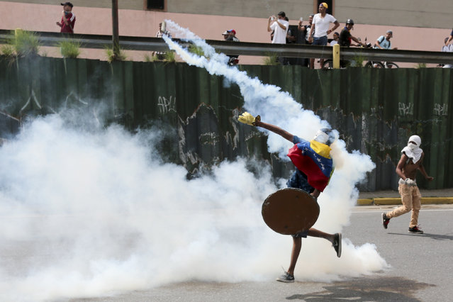 A demonstrator returns a canister of tear gas towards security forces during anti-government protests in Caracas, Venezuela, Wednesday, April 19, 2017. (Photo by Fernando Llano/AP Photo)