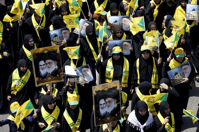 Iraqi Shiite Muslim women wave Iraqi Hezbollah flags during a parade marking the annual al-Quds Day, or Jerusalem Day, on the last Friday of the Muslim holy month of Ramadan in Baghdad, July 10, 2015. (Photo by Thaier al-Sudani/Reuters)