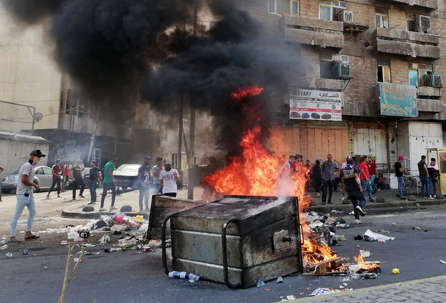 Anti-government protesters set a fire and block roads in Baghdad, Iraq, Wednesday, October 2, 2019. Security forces fired in the air and used tear gas Wednesday to disperse groups of demonstrators in Baghdad Wednesday, killing at least one and injuring six in renewed protests after violent confrontations between protesters and police a day earlier, officials said. (Photo by Hadi Mizban/AP Photo)
