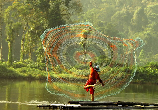 """The Net thrower"". The fisherman are conducting activities on Situgunung Lake. Photo location: Situgunung lake, Sukabumi, West Java, Indonesia. (Photo and caption by Dody Kusuma/National Geographic Photo Contest)"