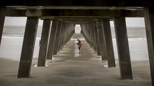 Danny James walks under the Tybee Island pier with a hat full of sea shells he collected during low tide as Hurricane Dorian passes 80 miles out to sea, September 5, 2019, in Tybee Island, Ga. (Photo by Stephen B. Morton/AP Photo)