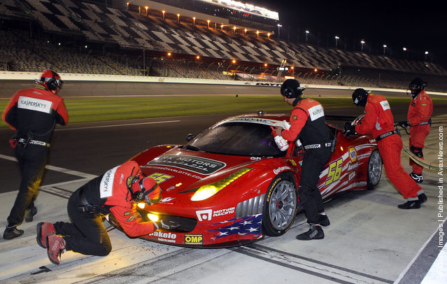 The #56 AF - Waltrip - Ferrari 458, driven by Robert Kauffman; Michael Waltrip; Travis Pastrana; Rui Aguas, pits in the early morning hours during the Rolex 24