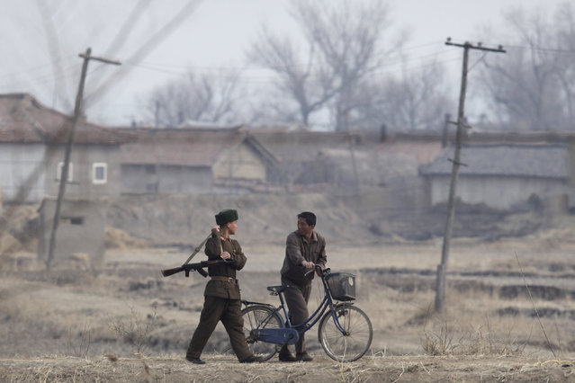 A North Korean soldier walks next to a farmer as he patrols the North Korean-Chinese border near the Chinese border city of Dandong April 4, 2009. (Photo by Nir Elias/Reuters)