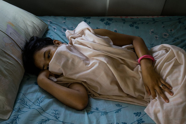 A young girl is seen in her bed in a halfway house outside of Manila. (Photo by Hannah Reyes Morales/The Washington Post)