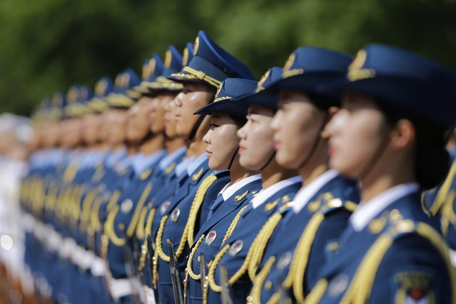 Female soldiers, as members of honour guards for the first time, stand in a line during a welcoming ceremony for Turkmenistan's President Gurbanguly Berdimuhamedov outside the Great Hall of the People, in Beijing, May 12, 2014. (Photo by Jason Lee/Reuters)