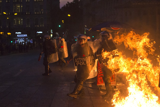 Riot police officers run away from fire as anti-austerity protesters throw petrol bombs during clashes in Athens, Wednesday, July 15, 2015. Greece's prime minister was fighting to keep his government intact in the face of outrage over an austerity bill that parliament must pass Wednesday night if the country is to start negotiations on a new bailout and avoid financial collapse. (Photo by Emilio Morenatti/AP Photo)