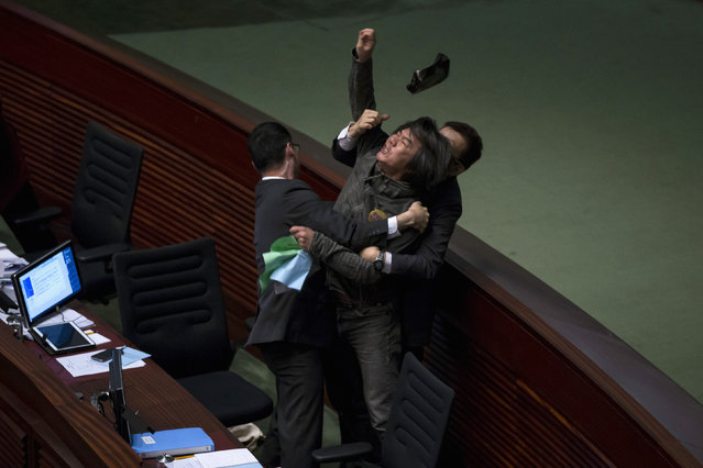 Pro-democracy lawmaker Leung Kwok-hung throws an object at Hong Kong's Financial Secretary John Tsang (not pictured) to demand a universal retirement protection scheme during the annual budget report at the Legislative Council in Hong Kong February 25, 2015. (Photo by Tyrone Siu/Reuters)