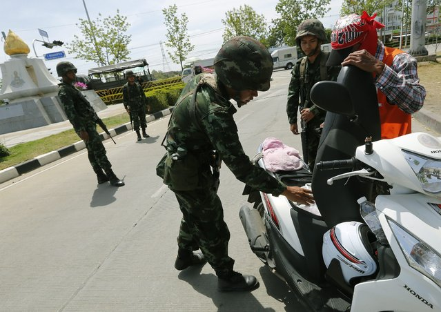Thai armed soldiers check a motorbike of a Red Shirts pro-government supporter at a checkpoint near a rally site on the outskirts of Bangkok, Thailand, 20 May 2014. (Photo by Narong Sangnak/EPA)