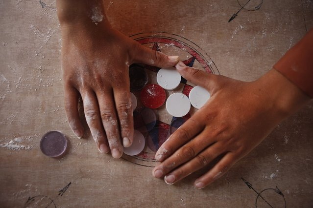In this Wednesday, July 8, 2015 photo, a boy arranges disks for a game of carrom during break time at a school in Kathmandu, Nepal. (Photo by Niranjan Shrestha/AP Photo)