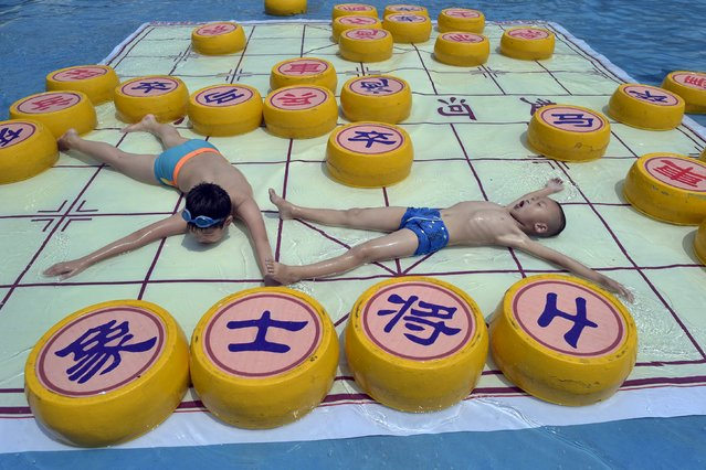 Children cool off on a 20 square meter Chinese chess board, at a water park in Chongqing municipality, July 7, 2015. (Photo by Reuters/China Daily)