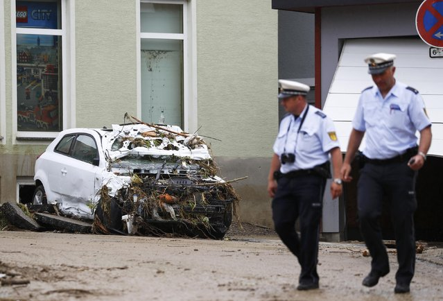 German policemen walk past a damaged car after floods in the town of Braunsbach, Germany, May 30, 2016. (Photo by Kai Pfaffenbach/Reuters)