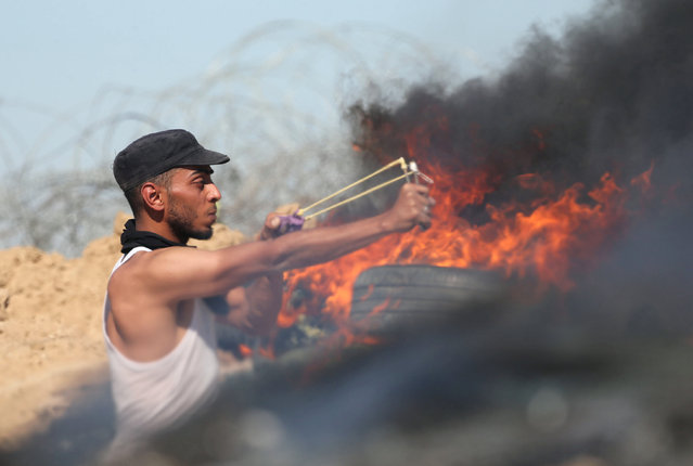 A Palestinian protester uses a slingshot to hurl stones towards Israeli troops during clashes near the border between Israel and Central Gaza Strip May 26, 2017. (Photo by Ibraheem Abu Mustafa/Reuters)