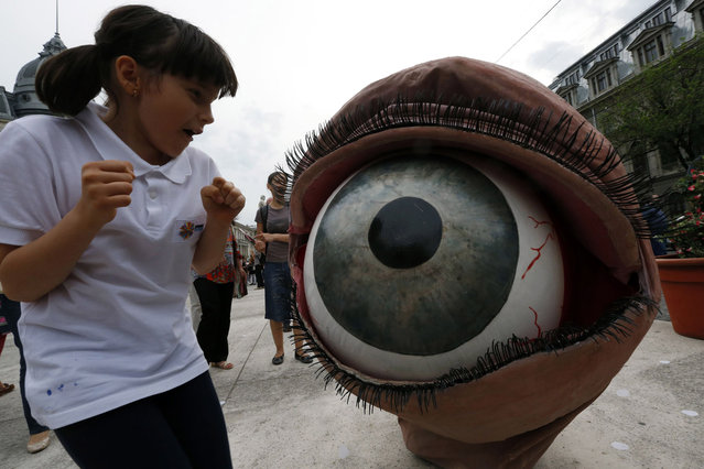 "A child reacts next to an Australian actor of Snuff Puppets theatre company costumed for ""Body Puppets"" performance during the ""B-Fit in the Street"" theatre festival in downtown Bucharest May 29, 2014. (Photo by Bogdan Cristel/Reuters)"