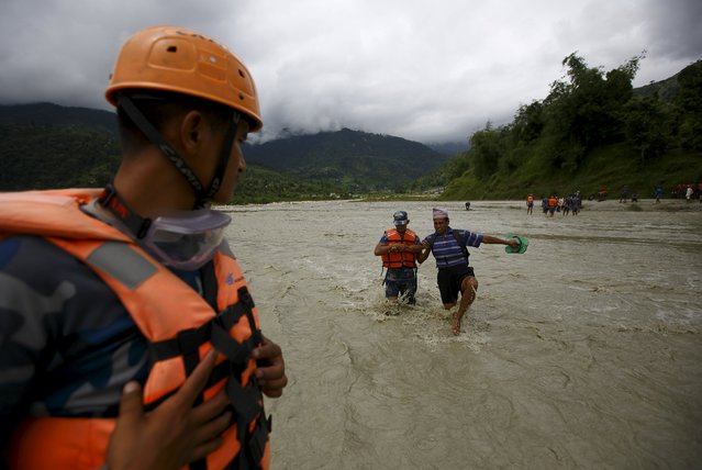 A rescue team member helps a villager to cross a flooded river after the trail bridge was washed away due to heavy rainfall in Kaski District July 31, 2015. (Photo by Navesh Chitrakar/Reuters)