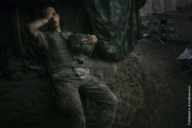 A soldier of Second Platoon, Battle Company of the Second Battalion of the US 503rd Infantry Regiment sinks onto an embankment in the Restrepo bunker at the end of the day