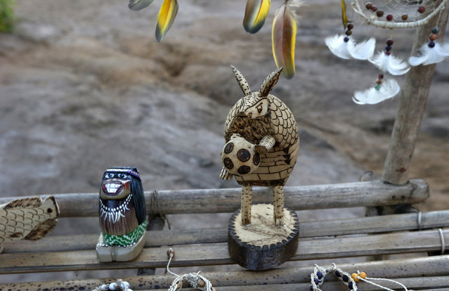 Crafts, including one depicting World Cup mascot Fuleco the Armadillo (R), made by members of the AmazonianTatuyo tribe are displayed in their village in the Rio Negro (Black River) near Manaus city, a World Cup host city, June 23, 2014. Because of their proximity to host city Manaus and their warm welcome, the Tatuyo have enjoyed three weeks of brisk business thanks to the World Cup. Usually, they host between 10 and 30 tourists a day. During the World Cup, this number has rocketed to 250 a day, They have become richer and other communities now come to them to sell them juices and fishes. (Photo by Andres Stapff/Reuters)
