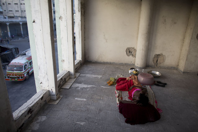 In this June 29, 2015 photo, Zarmor Sendi sleeps in an open room inside an abandoned, earthquake damaged government office building where she's living in Port-au-Prince, Haiti. During the day, Sendi inhabits one of the building's former bathrooms, too small to lie down in, and protected only by a thin curtain. Although the building's residents all know each other, there is no way to secure the site, leaving children and single women like Sendi particularly vulnerable. (Photo by Rebecca Blackwell/AP Photo)