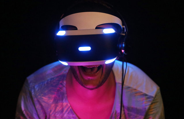 """A visitor tests the new """"Project Morpheus"""" 3D virtual reality glasses by Sony at the computer and video games fair Gamescom in Cologne, Germany, 05 August 2015. The trade show will run from 05 to 09 August 2015 in Cologne. (Photo by Oliver Berg/EPA)"""
