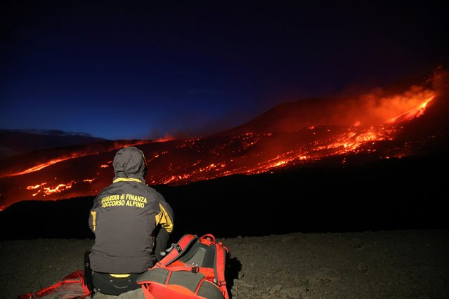 Member of the Guardia di Finanza alpine rescue looks on as Mount Etna, Europe's highest and most active volcano, erupts in Sicily, Italy, July 27, 2019. (Photo by Antonio Parrinello/Reuters)