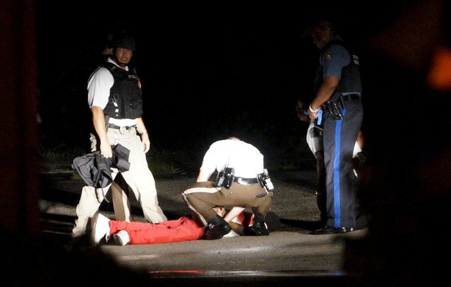 A black man lies dead with blood on his shirt after a police officer involved shooting in Ferguson, Missouri August 9, 2015. (Photo by Rick Wilking/Reuters)