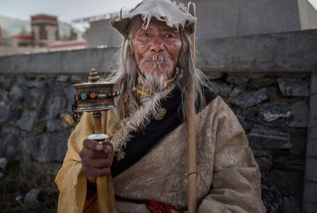 A ethnic Tibetan nomad uses a prayer wheel as he watches on July 24, 2015 at a local government sponsored festival on the Tibetan Plateau in Yushu County, Qinghai, China. (Photo by Kevin Frayer/Getty Images)