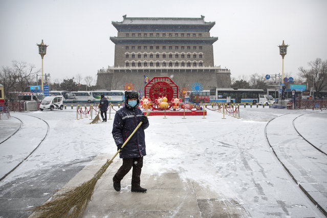 A maintenance worker wearing a face mask sweeps snow near Qianmen Gate during a snowfall in Beijing, Wednesday, February 5, 2020. Deaths from a new virus rose to 490 in mainland China on Wednesday while new cases on a Japanese cruise ship, in Hong Kong and in other places showed the increasing spread of the outbreak and renewed attention toward containing it. (Photo by Mark Schiefelbein/AP Photo)