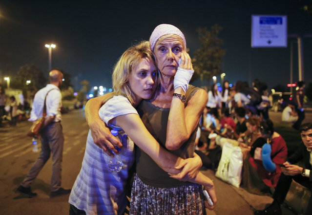 Passengers embrace each other as they wait outside Istanbul's Ataturk airport, early Wednesday, June 29, 2016 following their evacuation after a blast. (Photo by Emrah Gurel/AP Photo)