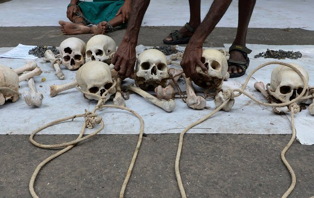 An Indian farmer from Tamil Nadu state arranges human skulls, said to belong to farmers who had committed suicide, during a protest in New Delhi on August 1, 2017. Farmers from Tamil Nadu are protesting in New Delhi with the bones of farmers who have committed suicide in the wake of a prolonged drought and rising amounts of debt, seeking action from the government including the write-off of bank loans and relief packages for drought affected areas. (Photo by Sajjad Hussain/AFP Photo)